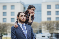 Portrait of displeased businessman and woman outside office building - JSCF00066