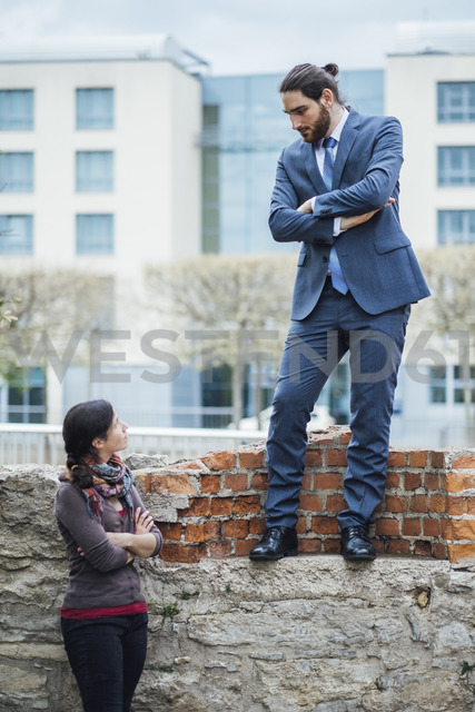 Businessman standing on a wall looking down at woman - JSCF00069