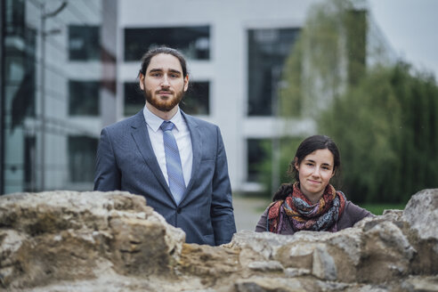 Portrait of businessman and woman behind a wall outside office building - JSCF00072