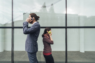 Businessman talking on cell phone with woman holding an apple at her ear - JSCF00081