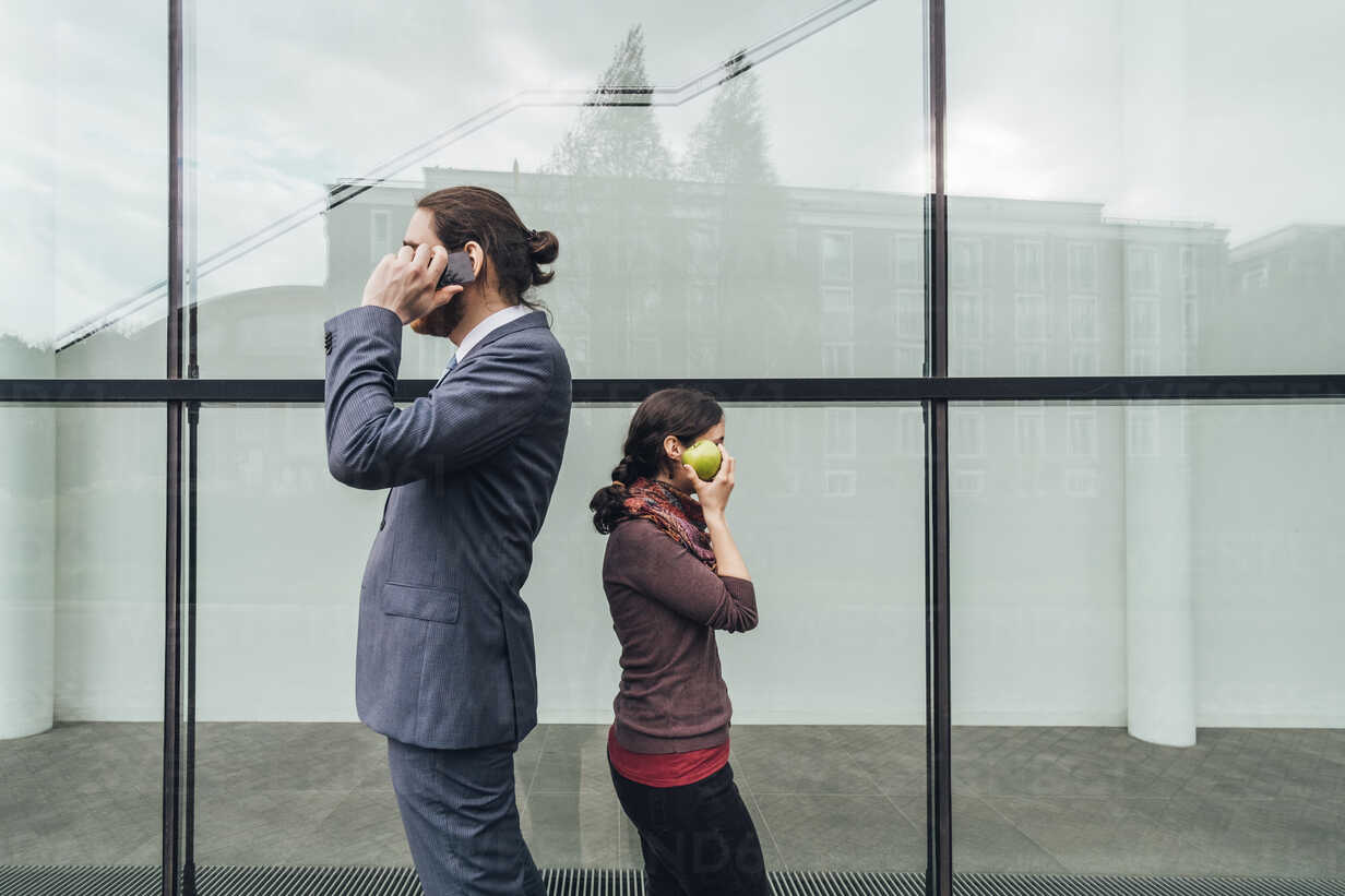 Businessman talking on cell phone with woman holding an apple at her ear - JSCF00081 - Jonathan Schöps/Westend61