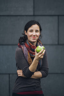 Portrait of smiling woman eating an apple - JSCF00084
