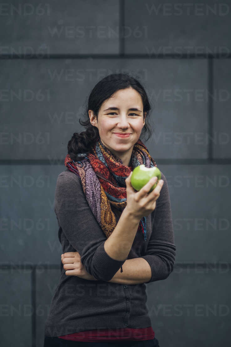 Portrait of smiling woman eating an apple - JSCF00084 - Jonathan Schöps/Westend61
