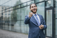 Portrait of happy businessman standing outdoors pointing his finger - JSCF00090