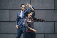 Happy businessman and woman dancing outdoors - JSCF00093