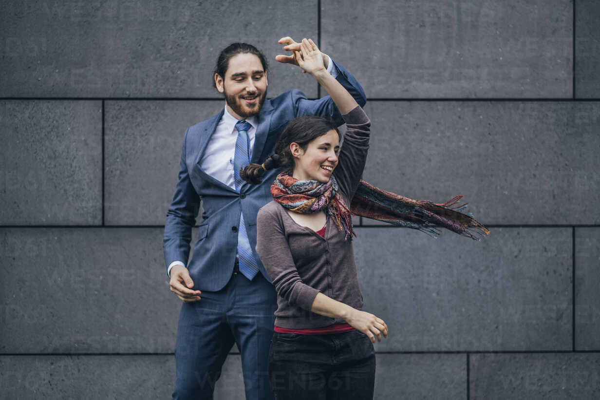 Happy businessman and woman dancing outdoors - JSCF00093 - Jonathan Schöps/Westend61