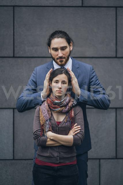 Businessman covering woman's ears - JSCF00096