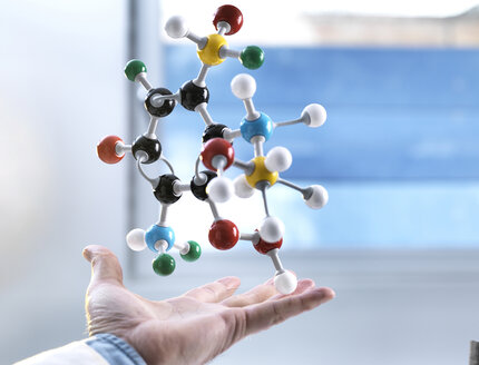 Hand and a floating molecular model, gravity - ABRF00126