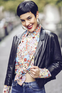Portrait of fashionable young woman wearing patterned blouse and leather jacket - JSMF00125