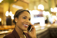 Businesswoman talking on cell phone in restaurant - CAIF16304