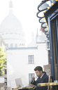 Businessman working at sidewalk cafe near Sacre Coeur Basilica, Paris, France - CAIF16331