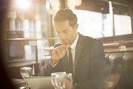 Businessman using digital tablet in restaurant - CAIF16334