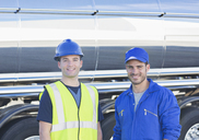Portrait of confident workers next to stainless steel milk tanker - CAIF16367