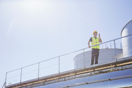 Worker using walkie-talkie on platform next to silage storage towers - CAIF16382