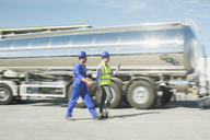 Businessman and worker walking along stainless steel milk tanker - CAIF16391