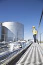 Worker using walkie-talkie on platform above stainless still milk tanker - CAIF16394