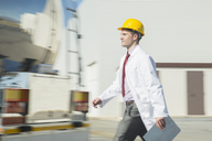 Scientist in hard-hat walking with clipboard - CAIF16397