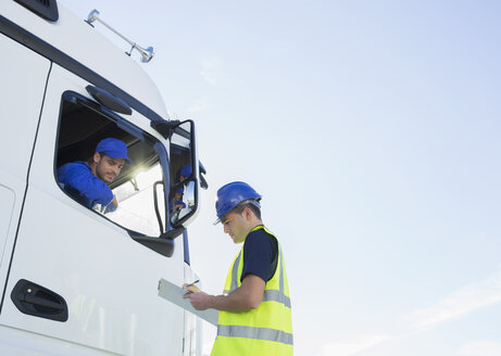 Worker with clipboard talking to truck driver - CAIF16409