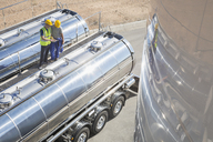 Workers on platform above stainless steel milk tanker - CAIF16412