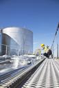 Worker on platform above stainless steel milk tanker - CAIF16415