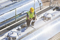Worker using digital tablet on top of stainless steel milk tanker - CAIF16421
