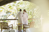 Couple in bathrobes standing in outdoor spa - CAIF16523
