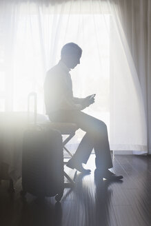 Businessman using cell phone in hotel room - CAIF16589