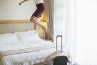 Businesswoman jumping on bed in hotel room - CAIF16625