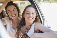 Sisters laughing in car backseat - CAIF16724