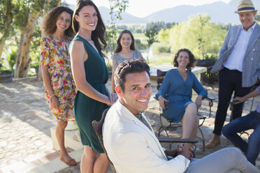 Family gathered on backyard patio - CAIF16736