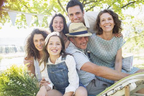 Family hugging outdoors at picnic - CAIF16763