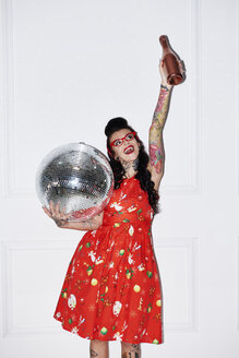 Portrait of tattooed woman with champagne bottle and disco ball - ABIF00136