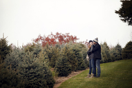 Affectionate couple on field by Christmas tree farm - CAVF08322