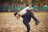 Man carrying woman on shoulder while standing at park - CAVF08355