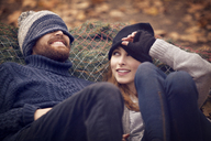 Woman looking at man wearing knit hat while leaning on Christmas Tree - CAVF08358