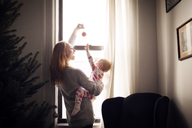 Woman playing with baby girl while standing by window at home - CAVF08361