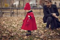 Man looking at girl walking on field - CAVF08370