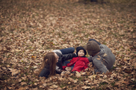 Parents with baby relaxing on field in park - CAVF08376