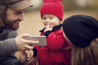 Father showing smart phone to baby at park - CAVF08379