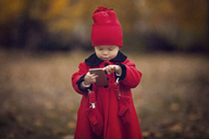 Cute baby girl using smart phone while standing on field - CAVF08385