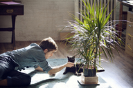 Man playing with cat while lying on floor at home - CAVF08391