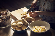 High angle view of woman cutting potatoes on cutting board at home - CAVF08400