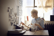 Woman sticking photographs on wall while sitting by table at home - CAVF08406