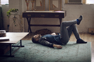 Side view of man lying on carpet at home - CAVF08427