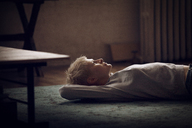 Woman looking up while lying on carpet at home - CAVF08430