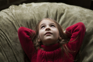 Girl looking up while reclining on bean bag at home - CAVF08463