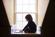 Boy using laptop computer while sitting by window at home - CAVF08478