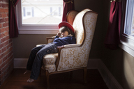 Boy wearing hat sitting on armchair at home - CAVF08481