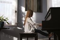 Side view of girl playing piano at home - CAVF08484