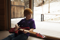 Boy holding guitar while looking through window at home - CAVF08526